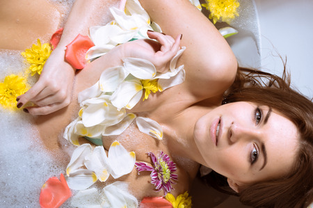 young girl bath: Spa body care for sensual relaxation: picture of beautiful sexy young woman pinup girl having fun relaxing in bath with flowers petals on milk copy space water background.