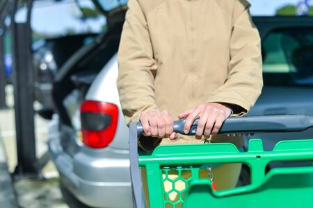 woman shopping cart: Young woman holding shopping push cart closeup picture of hands with car on background