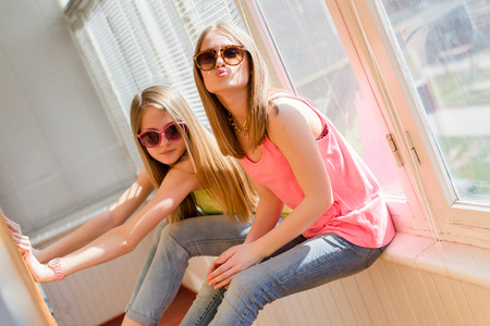 closeup portrait of hugging 2 beautiful blond young women having fun happy smiling on sunny windows background