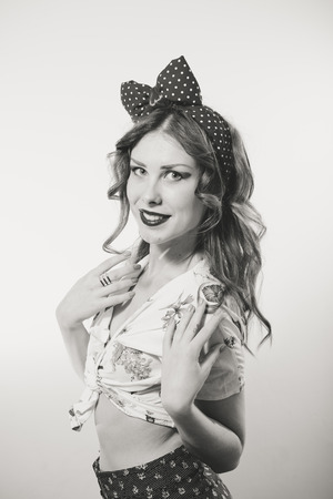 bandana girl: Portrait of a beautiful blond pin up girl with ponytail and bandana  looking amazed holding her hand near her mouth black and white Stock Photo