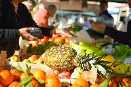 groceries: Buyer shopping for groceries. Pineapple with fruits on grocery market stall background