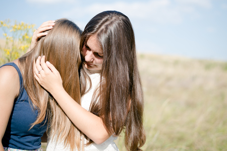mourn: one comforts and expressing feelings of compassion for another: Two teenage girls,  beautiful young women girl friends having difficult times on the summer outdoors background closeup portrait