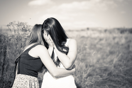 Black and white picture of one girl comforting and expressing feelings of compassion for another: beautiful young women girlfriends having difficult times on summer outdoors background