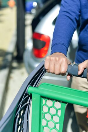 push cart: Closeup picture of male hand holding shopping push cart on car parking