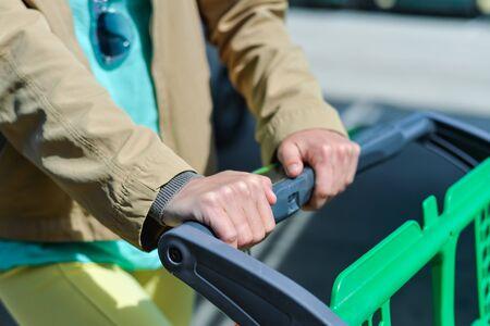comida rica: Mujer joven que sostiene la cesta de la compra empuje foto de primer plano de las manos con el coche en el fondo Foto de archivo