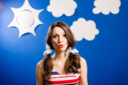 Portrait of happy smiling pretty young woman showing kissing lips over blue paper sky with white clouds copy space background Stock Photo