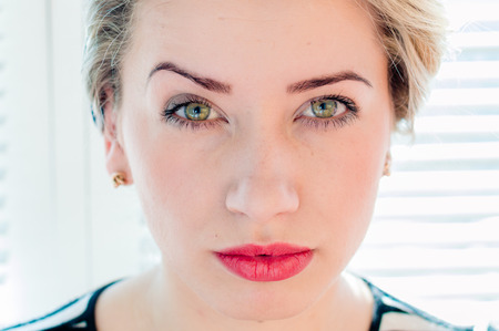 looking towards camera: Closeup image of cute blond pinup woman face with green eyes looking pensively towards camera