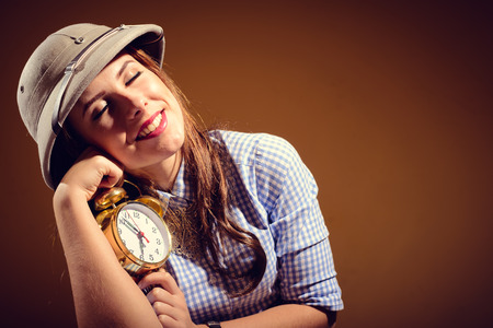 pith: Young beautiful woman wearing a pith helmet embracing alarm clock sleepy, brown background with copy space.