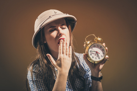 pith: Young beautiful woman wearing a pith helmet holding alarm clock sleepy yawning, brown background with copy space.