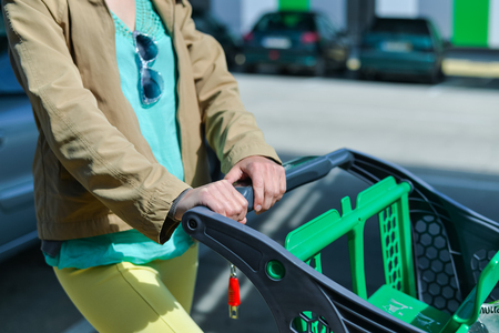 push cart: Young woman holding shopping push cart closeup picture of hands with car on background
