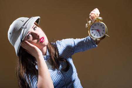 pith: Sad shocked young woman in checkered shirt and pith helmet holding alarm clock over brown background
