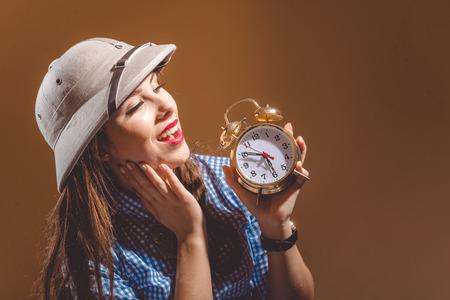 médula: hermosa mujer joven que llevaba un casco de médula abrazar reloj despertador con sueño fondo, marrón, con copia espacio.