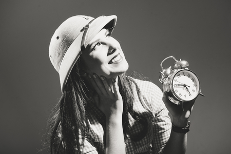 pith: Funny surprised young woman in checkered shirt and pith helmet holding alarm clock black and white image