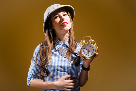 pith: Fuuny young woman in checkered shirt and pith helmet holding alarm clock over brown background