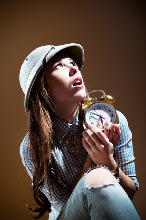 m�dula: Funny surprised young woman in checkered shirt and pith helmet holding alarm clock over brown background Foto de archivo