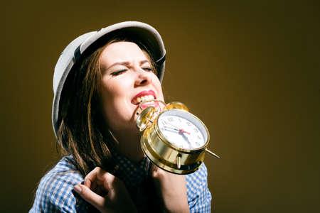 médula: mujer joven sorprendida triste en camisa de cuadros y la celebración de casco de médula reloj de alarma sobre fondo marrón