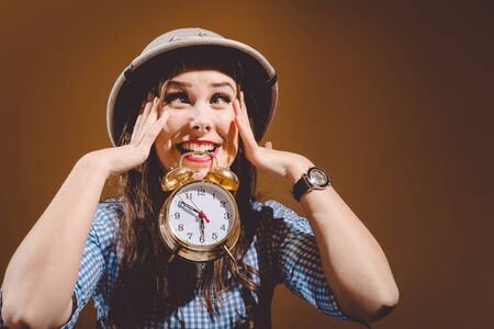 pith: Funny surprised young woman in checkered shirt and pith helmet holding alarm clock over brown background Stock Photo