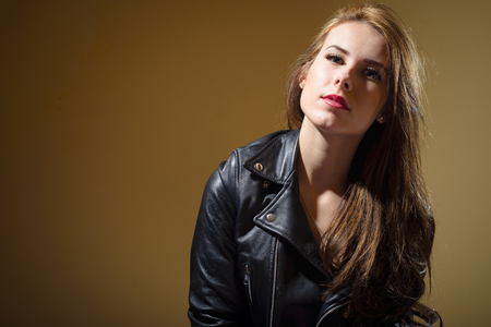 Beautiful young woman in black leather jacket on brown background, closeup portrait