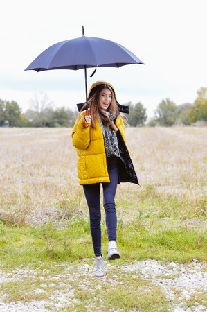Young beautiful brunette woman having fun with umbrella wearing warm yellow coat or puffer on copy space outdoors background photo