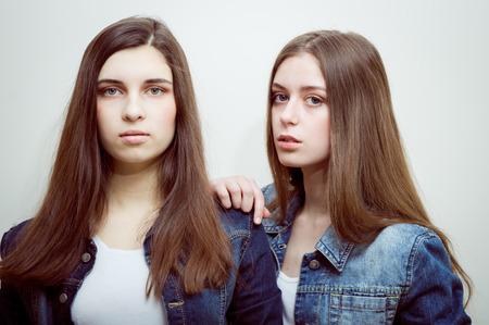 jeune fille adolescente nue: photo de mode de deux belles jeunes femmes avec de longs cheveux noirs et maquillage naturel porter des jeans vêtements décontractés, posant en studio