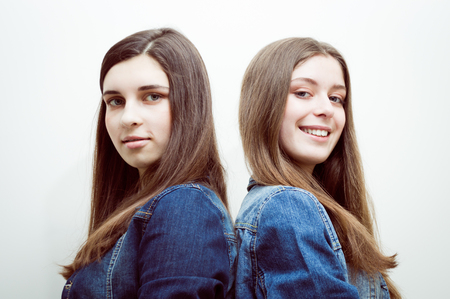 parentheses: Closeup portrait of two beautiful young women with long dark hair and natural makeup wearing jeans shirts happy smiling looking at camera