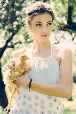 Beautiful happy smiling young woman holding a live little red chicken in nature summer background photo