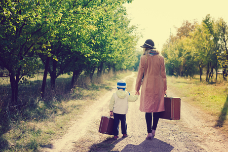 Back view of female wearing hat with child walking away on rural road. They carrying old suitcase over sunny outdoors background photo