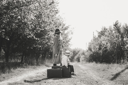 Black and white image of female wearing hat with child walking away on rural road back view. They are carrying old suitcase over sunny autumn outdoors background photo