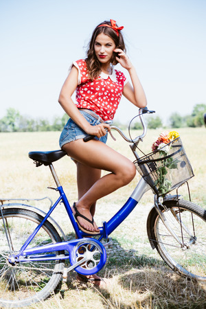 road of love: Young beautiful brunette pinup woman cycling in fields under bright blue summer sky copy space image