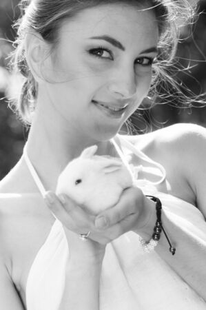 Black and white image of smiling woman holding a little cute white bunny rabbit photo