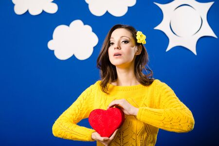 boxing day: Happy pretty girl in yellow sweater with red heart shaped present box, portrait over bluescreen background with paper clouds and sun