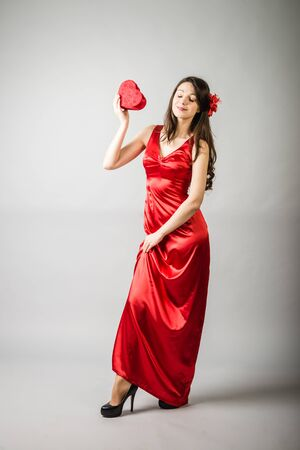 Color full length portrait of posh sexy woman in long red silk dress over white background holding present box Stock Photo
