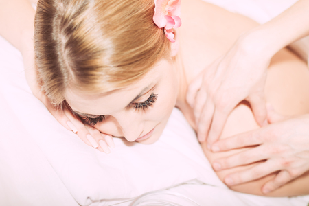 Attractive young blond lady relaxing on white and getting a spa massage