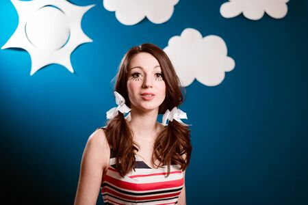 dreaminess: Portrait of happy smiling pretty young woman over blue paper sky with white clouds copy space background