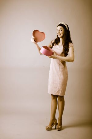 oriented: Brunette girl with gift bow of heart shape for Valentines Day. Full length portrait vertical oriented color image Stock Photo