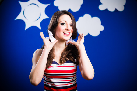 Closeup portrait of happy smiling beautiful young woman looking funny over blue screen background with paper sun and clouds photo