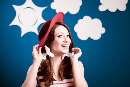 Portrait of happy smiling pretty young woman in red hat over blue paper sky with white clouds copy space background photo