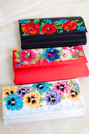 Needlework. Colorful gift bags for jewelry embroidered satin handmade purse Stock Photo
