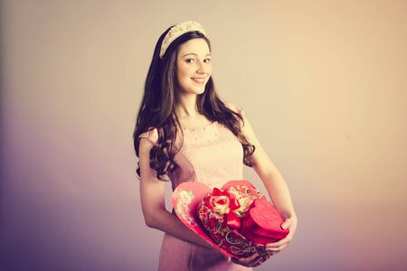 Sepia image of happy woman in love with gift box for Valentines Day. Middle length photo on neutral background photo
