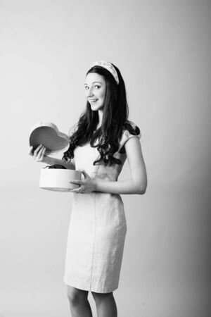 Young woman holding a present box of heart shape black and white image photo