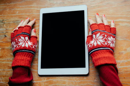 pc screen: Womans hand with red wool glove with tablet pc on wood background ready for Christmas Stock Photo