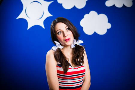 Amazed excited young woman actress on the theatrical play handmade blue sky background Stock Photo