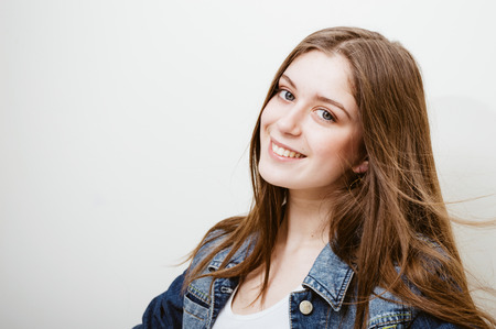 Attractive joyful young woman with waving hair wearing jeans jacket and healthy smiling. Fashion cheerful lifestyle, leisure concept on light background