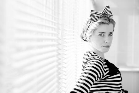 jalousie: Black and white portrait of pinup girl attractive blond woman having fun posing looking at camera on sun lighting blinds windows background