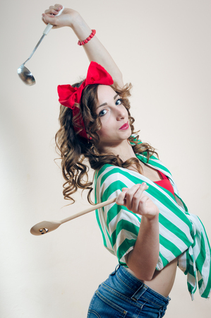 Joyful cooking with ladle and spatula: portrait of charming pinup girl attractive woman in polka dots having fun happy smiling looking at camera on white copy space background