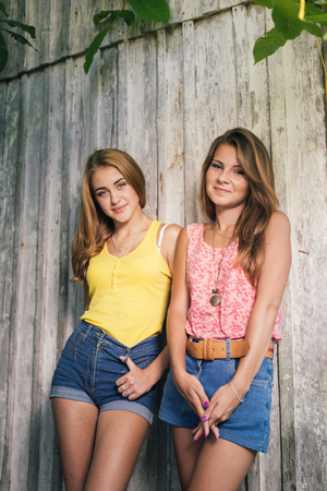 Two happy teenage girls friends wearing Tshirts and jeans shorts smiling over pale wooden background Stock Photo