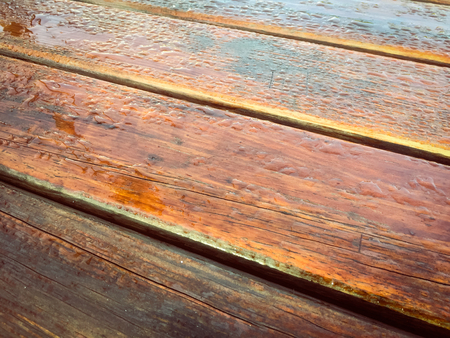 Close up on natural grungy weathered wood detail and drops of rain decorative textured background