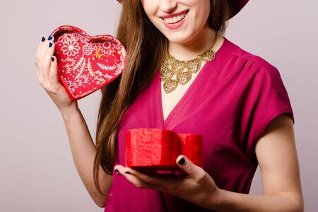 Joyful attractive positive woman holding gift box on light background. Closeup portrait of excited cheerful pretty lady