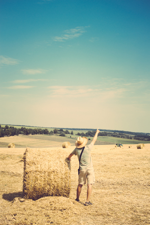 Back view of man standing by the round wheat bale on sunny landscape blue sky outdoors background Stock Photo