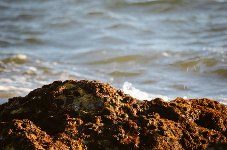 Natural sunny splashes on rocky shore outdoors seascape. Coastline abstract background Stock Photo